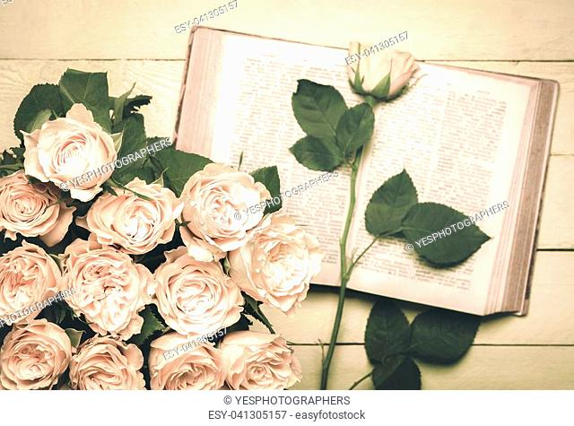 Vintage image with a bouquet of roses in the foreground and an old open book with a single rose on it in the background, placed on a wooden table
