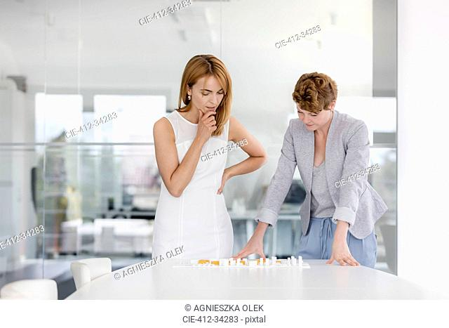Female architects examining model in conference room