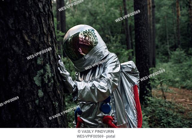 Spaceman exploring nature, examining tree trunk
