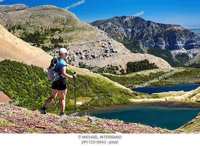 Female hiker walking down a rocky hillside with alpine lake below and mountains in the distance with blue sky; Waterton, Alberta, Canada