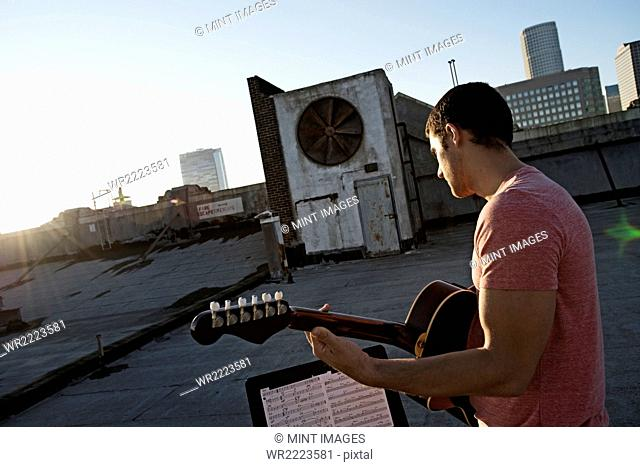 A man playing a guitar, sititng on a rooftop terrace overlooking the city at dusk
