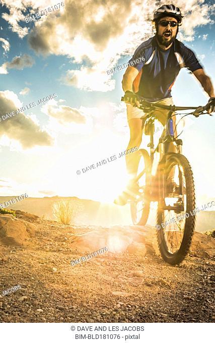 Hispanic man riding bike on remote trail