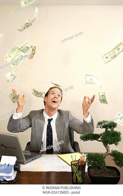 Businessman tossing dollar bills in the air