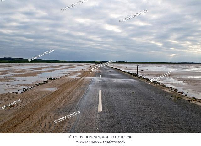 Sand covered road to Lindisfarne - Holy island at low tide, Lindisfarne, England  The road is only passable for a few hours around low tide