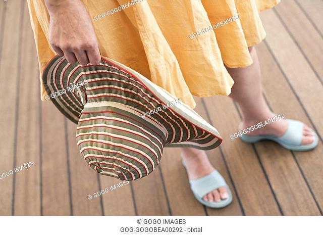 Woman holding sunhat