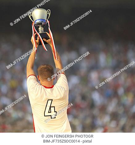 Male soccer player triumphantly holding up trophy