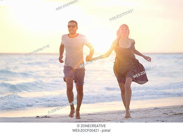 Young couple running on the beach, holding hands