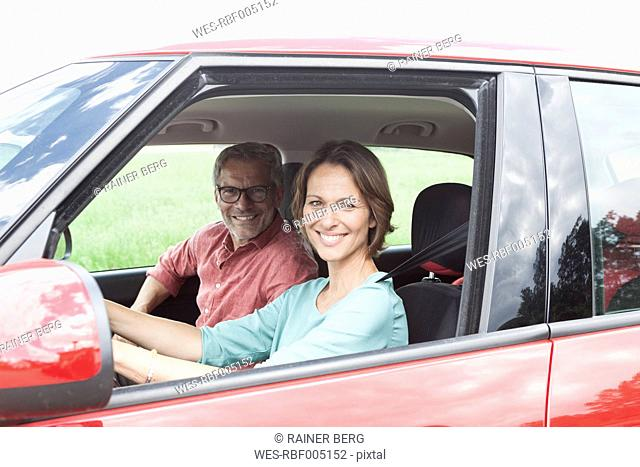 Portrait of happy mature couple in car