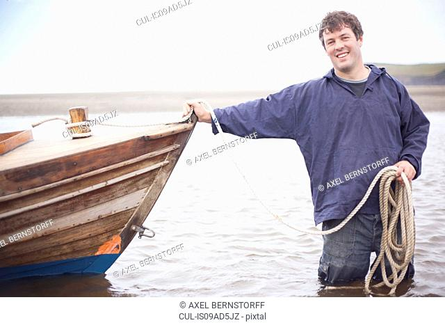 Portrait of man holding rope leaning on rowing boat, Wales, UK