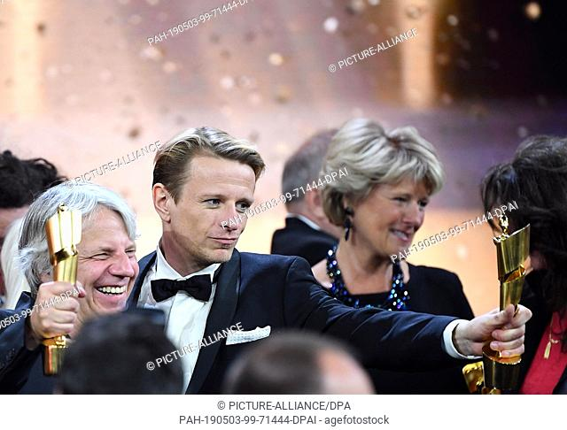 """03 May 2019, Berlin: Director Andreas Dresen (l) and actor Alexander Scheer (M) from the film """"""""Gundermann"""""""" show their trophies after the 69th German Film..."""