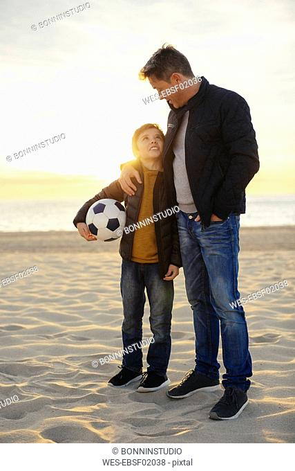 Father embracing son with football on the beach at sunset
