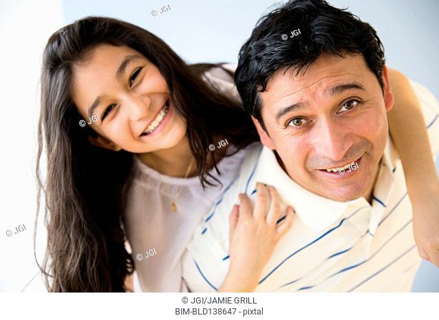 Hispanic father carrying daughter piggyback