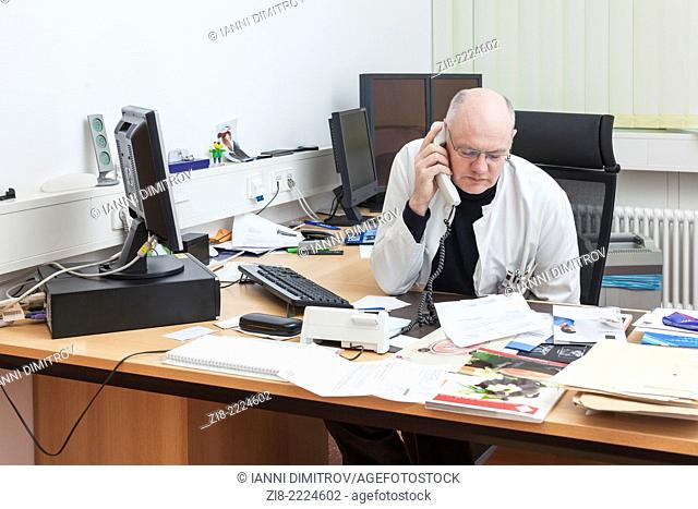 Doctor at his desc talking on the telephone