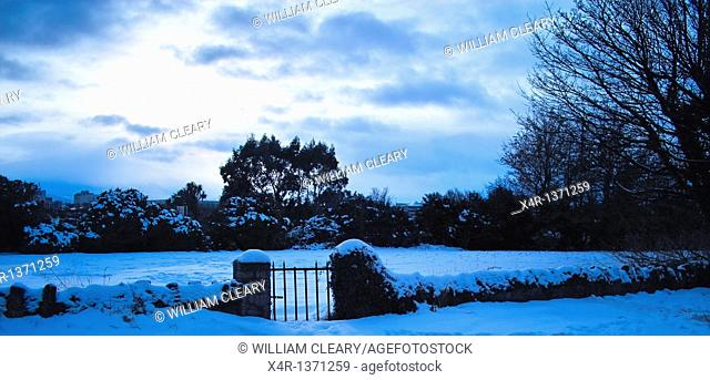 Garden gate and snow covered landscape, Clontarf, Dublin, Ireland