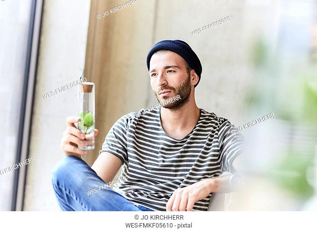 Thoughtful young man holding plant in a jar