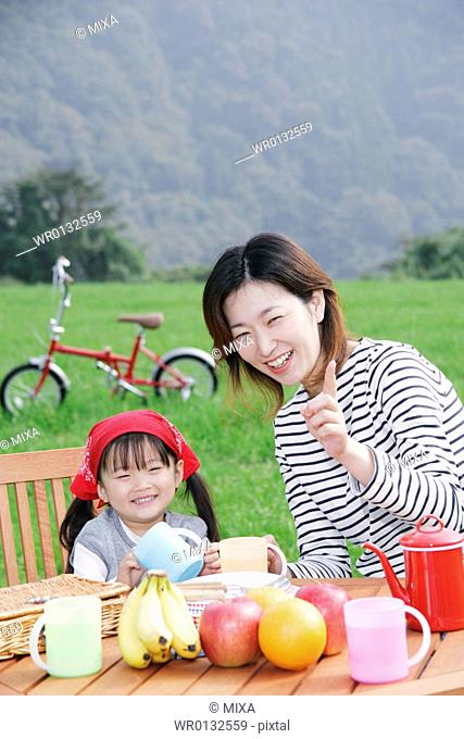Mother and daughter sitting at picnic table