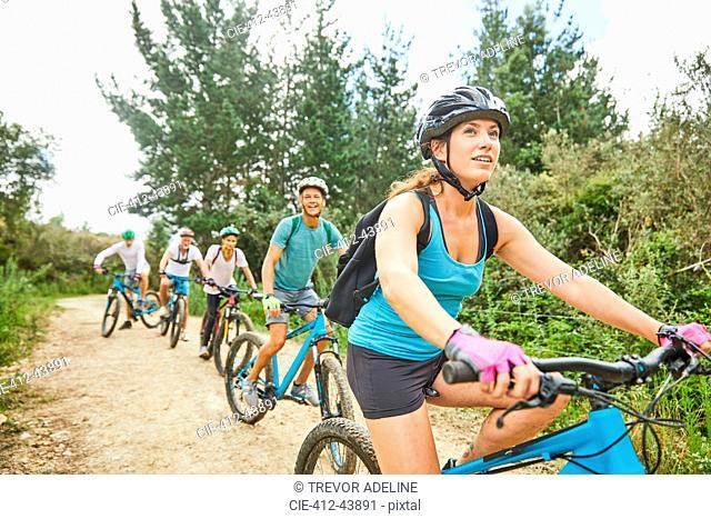 Friends mountain biking on trail