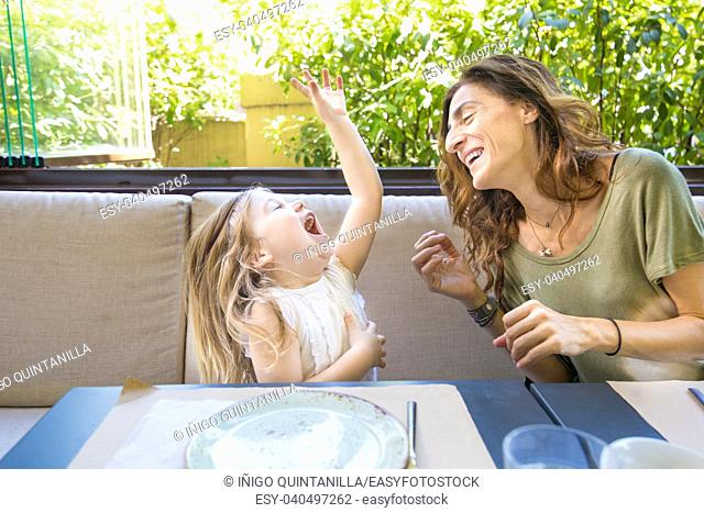 happy family in restaurant: woman mother and her daughter four years old blonde girl laughing out loud with funny face expression