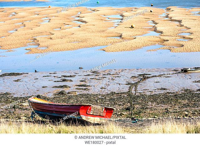 Colourful boats marooned on sandbanks at low tide on East Fleet river estuary at Wells next the sea, North Norfolk coast, East Anglia, England, UK