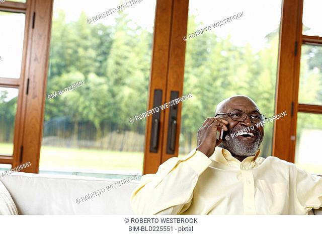 Black man talking on cell phone on sofa
