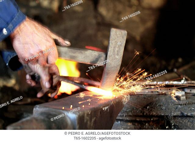 Blacksmith forge pounding and shaping a turning plow