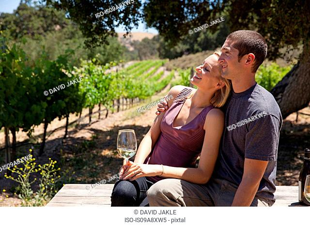Young couple in vineyard, woman with white wine