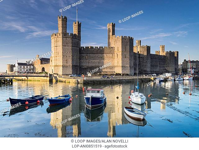 Boats moored at high tide in the harbour below Caernarfon Castle