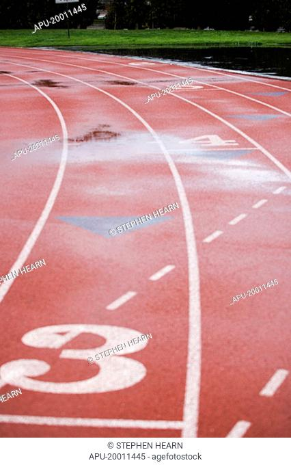 Athletic track lanes at stadium wet with reflection