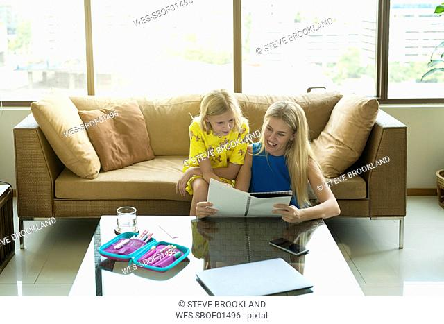 Happy mother and daughter sitting on a couch looking at the girl's homework together