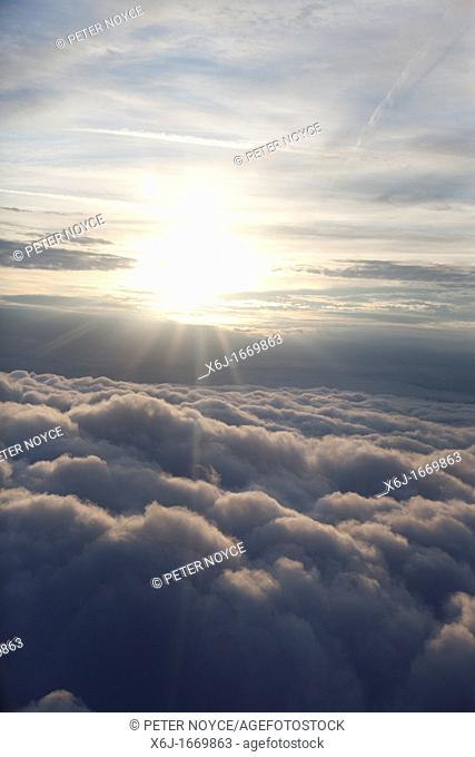 sun above sky from an aircraft with blanket of cloud