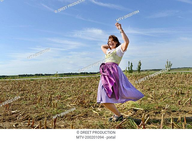 Mature woman dancing in field, Bavaria, Germany
