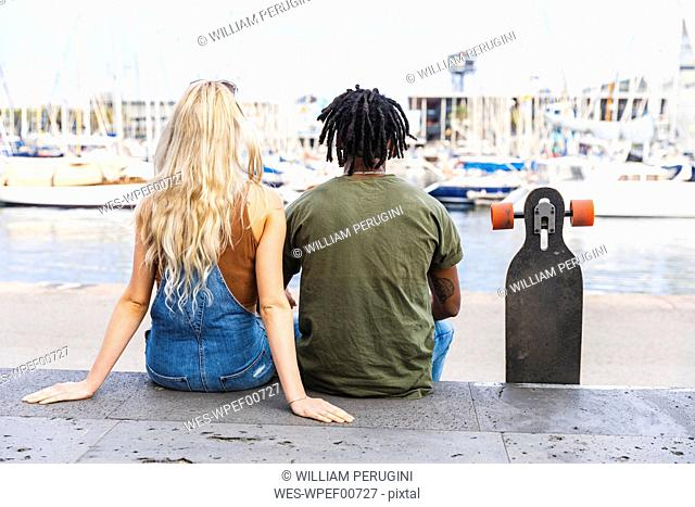 Spain, Barcelona, back view of multicultural young couple sitting side by side with longboard at marina