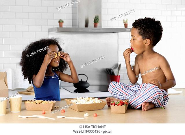 Little girl covering her eyes with cookies while brother watching her