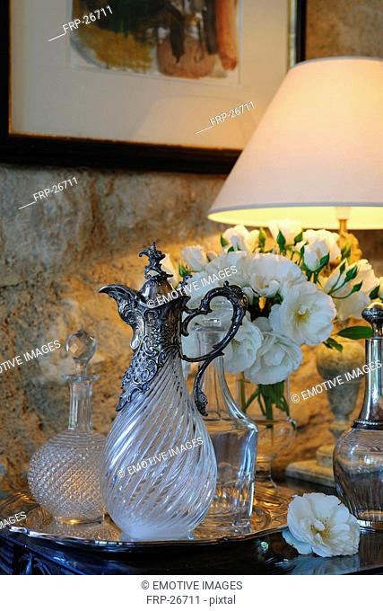 Carafe, bunch of flowers and lamp on dresser