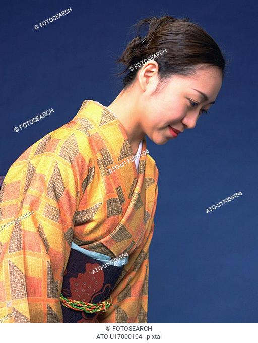 A woman in kimono bowing, Side View