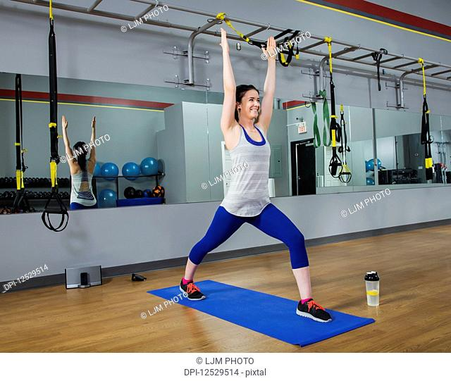 A fitness trainer doing a warrior 1 yoga pose at a gym; Spruce Grove, Alberta, Canada