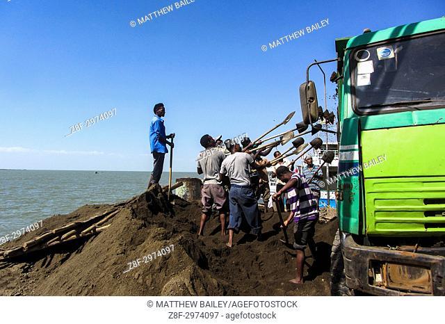 Construction workers shovel dirt in Bahir Dar, Ethiopia