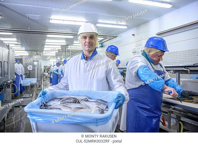 Worker holding bucket of fish in factory