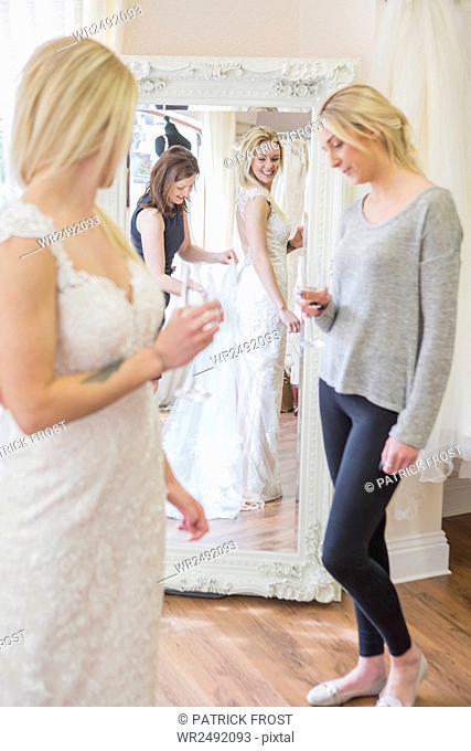 Female customer in bridal shop trying on wedding dress