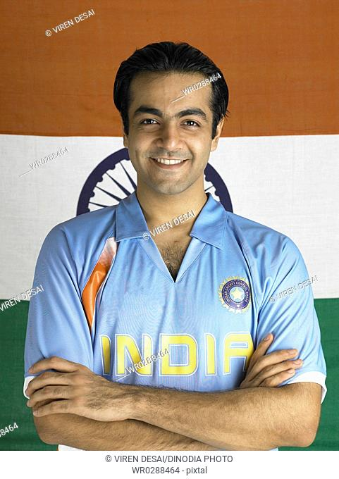 Indian cricket player standing with hands folded in front of flag of India in background MR702A