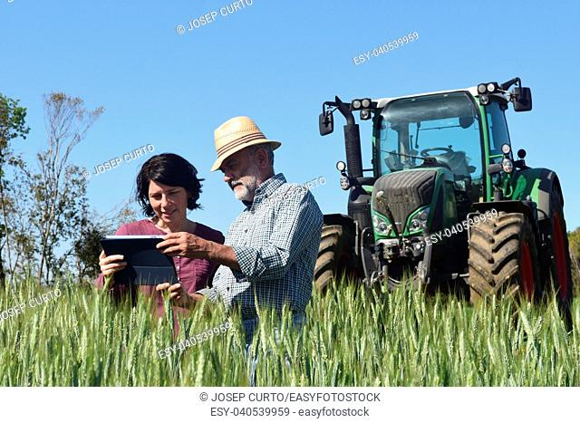 couple of farmers in a field with a digital tablet.Porqueres, Girona province, Spain