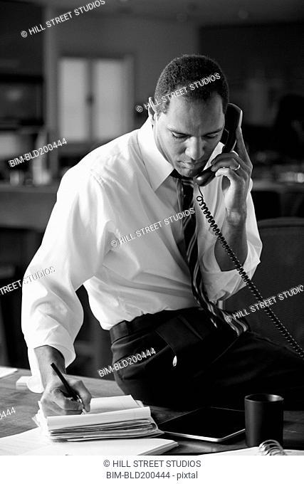 Mixed race businessman talking on telephone