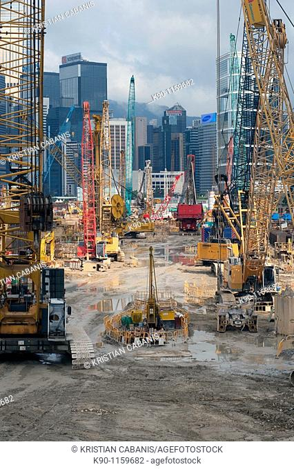 Heavy construction equipment nicely arranged on a land reclamation project in Hong Kong with a view through to the skyscrapers of Central in the background
