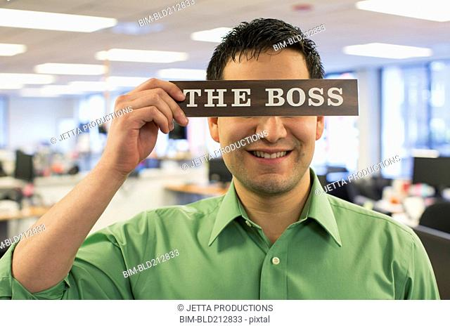 Hispanic businessman holding 'The Boss' sign over face