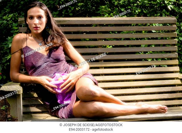 Portrait of a 27 year old brunette woman in a summer dress sitting on a bench looking at the camera in an outdoor setting holding a bowl of grapes
