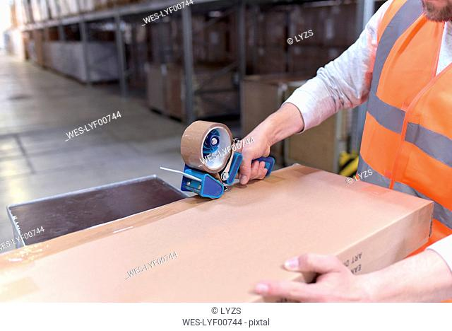 Man in factory hall wearing safety vest closing cardboard boax
