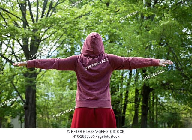 Young woman, arms extended, her back to the camera, wearing a red sweatshirt and hoodie, and standing in front of trees in a park