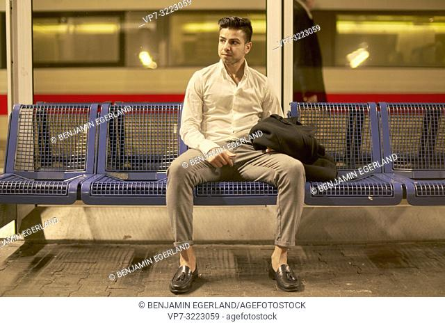 young man sitting on bench at train station, in Munich, Germany