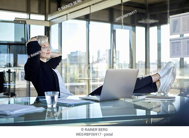 Businesswoman sitting at desk in office with closed eyes