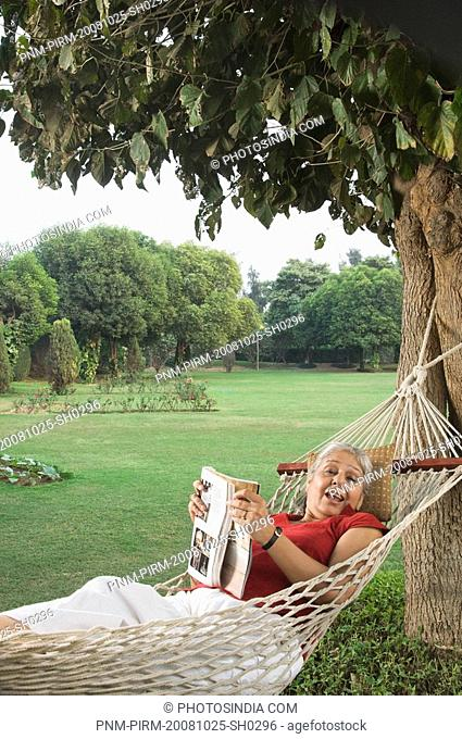 Woman lying in a hammock with a magazine, New Delhi, India